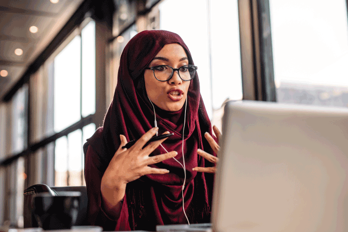 Woman wearing a hijab and glasses having a video chat conversation