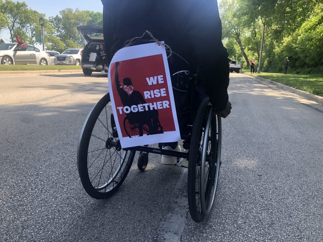 "Poster that says ""We rise together"" attached to the back of a wheelchair"