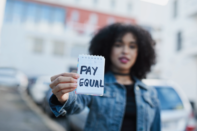 "Woman holding up a piece of paper that says ""Pay Equal"""
