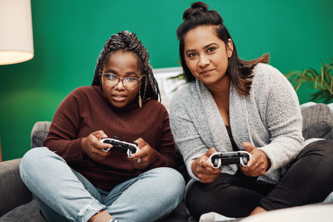 Two women of color playing a video game