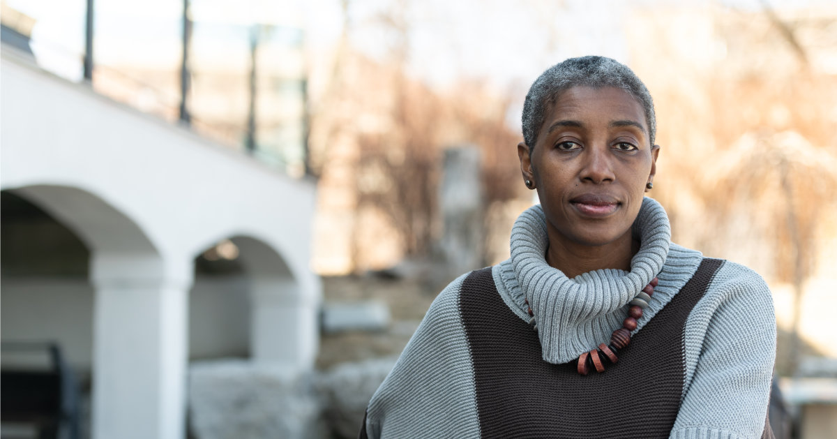 A senior woman of African descent sits outside while looking contemplative. She is dressed warmly in her sweater and looks cozy. She is looking into the camera.