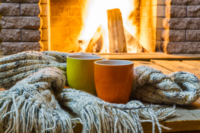 Two mugs in front of a fireplace