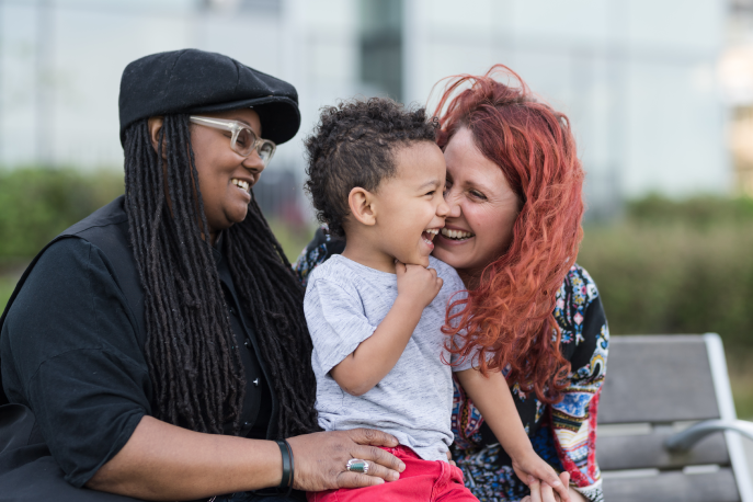 Two women holding and laughing with their child