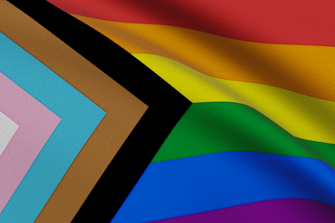 Pride flag with black and brown stripes and the transgender flag incorporated