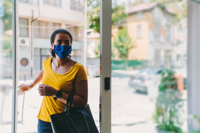 Woman wearing a face mask entering a building