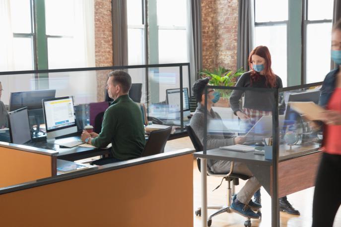People wearing masks working in an open-plan office