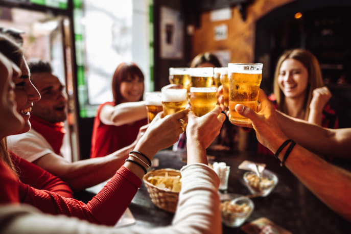 """Group of people in a bar holding up their glasses to """"cheers"""""""
