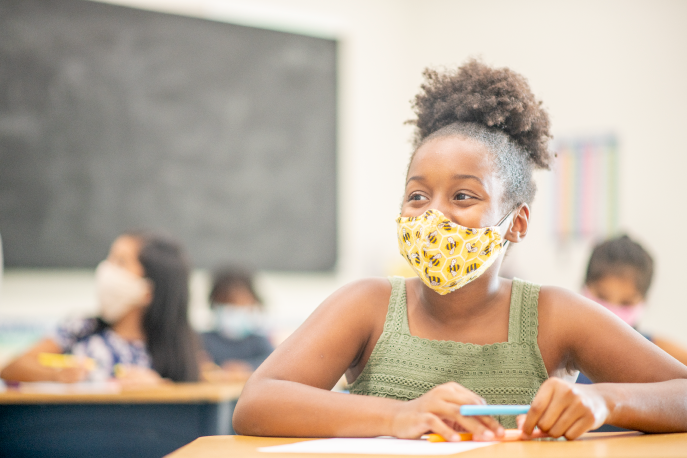 Young student in a classroom wearing a mask